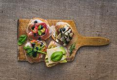 Antipasti brusquetta set on a rustic wooden board over a sackcloth surface Stock Photos