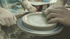 A potter's hands show the child how to work to help him to work with the ceramic Stock Footage