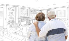 Curious Senior Couple Looking Over Custom Living Room Design Drawing. Stock Photos