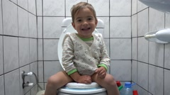 Cute child on toilet bowl open arms Stock Footage