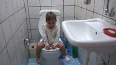 Cute child sits on toilet bowl Stock Footage