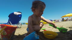 Little Boy Making a Sandcastle on the Beach on a Summer Day - stock footage