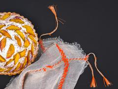 Peach pie with sugar powder over a linen table cloth on a dark background - stock photo