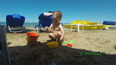 Cute Little Boy Playing with Sand on the Beach - stock footage
