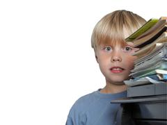 Six year old boy surrounded by piles of books isolated - stock photo