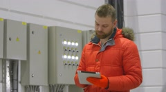 The engineer checks the voltage on the tablet Stock Footage