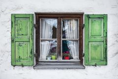 Authentic window with green wooden shuttters in a small town of Stock Photos