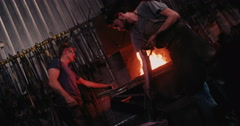 Blacksmith working in metal industry forging iron at furnace - stock footage