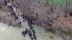 Hundreds of migrants and refugees cross a river, north of Idomeni, Greece Stock Footage