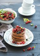 Breakfast set. Buckwheat pancakes with fresh berries and honey on rustic plat Stock Photos