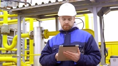 Engineer holding a tablet, talking on walkie-talkie in modern industrial factory Stock Footage