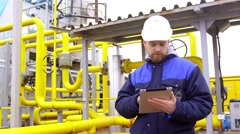 Stock Video Footage of engineer holding a tablet, talking on walkie-talkie and smiling at camera in