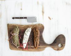 French alsacian smoked salamis on rustic wooden chopping board over white bac - stock photo