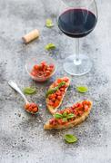 Wine appetizer set. Glass of red wine, brushettas with fresh tomato and basil Stock Photos