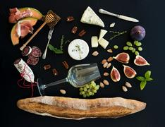 Wine and snack set. Baguette, glass of white, figs, grapes, nuts, cheese vari Stock Photos