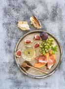 Wine appetizer set. Glass of white wine, honeycomb with drizzlier, figs, melo Stock Photos