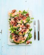 Prosciutto, melon, fig and soft cheese salad on a white serving board over gr Stock Photos