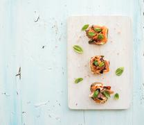 Bruschettas with Prosciutto, roasted melon, soft cheese and basil on white wo Stock Photos
