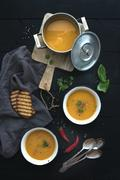 Red lentil soup with spices, herbs, bread in a rustic metal saucepan and bowl Stock Photos