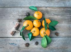 Fresh mandarines with cinnamon sticks and anise stars over a rou Stock Photos