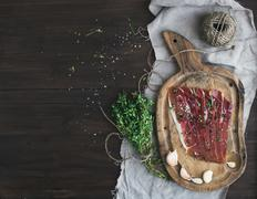 Cured pork meat prosciutto on a rustic woodem board with garli - stock photo