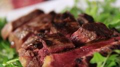 Serve steak slices:putting salt over sliced beef and green salad - stock footage