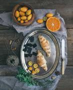 Rustic breakfast set: chocolate croissants on metal dish, fresh kumquats, ora Stock Photos