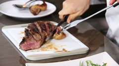 close up on hands Slicing of a grilled steak on a cutting board: slicing an beef - stock footage