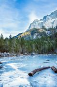 Frozen forest lake in Bavarian Alps near Eibsee lake, winter - stock photo
