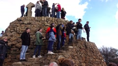 People climb up stony tower, topmost point of Park Guell, three cross atop Stock Footage