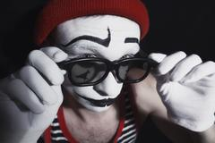 Mime wearing red hat and eyeglasses - stock photo
