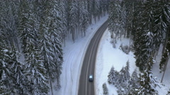 Aerial - Tilting down to a road with driving cars among snowy pine tree forest - stock footage