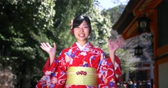 Beautiful Japanese Girl in Kimono waves at the camera infront of temple - stock footage