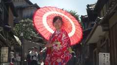 Beautiful young Japanese girl wearing Kimono spins Parasol in Kyoto Stock Footage