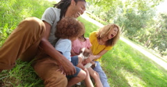 Multi-ethnic family spending time at park with new adorable pet - stock footage
