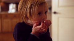 Little girl in the kitchen eating powdered sugar out of her hands Stock Footage