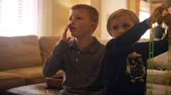 Brother and sister watching television together in the living room Stock Footage