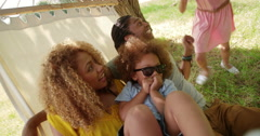 Photogenic Multi-ethnic family relaxing together on a hammock Stock Footage