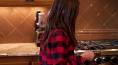 Girl measuring hot water from the kitchen sink into a mixing bowl Stock Footage