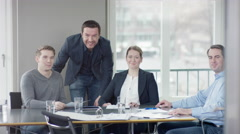 Group of businesspeople in a meetingroom looking into to camera Stock Footage