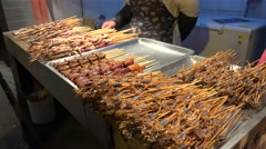 Fried scorpion and other exotic food on a stick at the Wangfujing snack street. - stock footage
