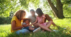 Stunning african-american family relaxing under a tree in park - stock footage