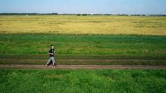 AERIAL: Running athlete man. Male runner jogging outdoor. Sport - stock footage