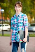 Portrait of young alluring woman holding education books. Student girl - stock photo
