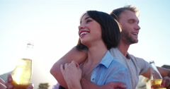 Hipster couple cuddling outside on a rooftop at sunset - stock footage
