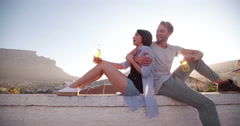 Hipster style young couple enjoy a beer on the rooftop - stock footage