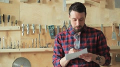 Man in the carpenter's workshop writing a draft on paper Stock Footage