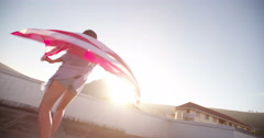 Teenage girl spinning around with an American flag on rooftop - stock footage