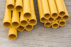 Stack of yellow PVC pipes - stock photo