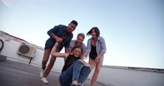 Group of friends having fun a the rooftop with a skateboard Stock Footage